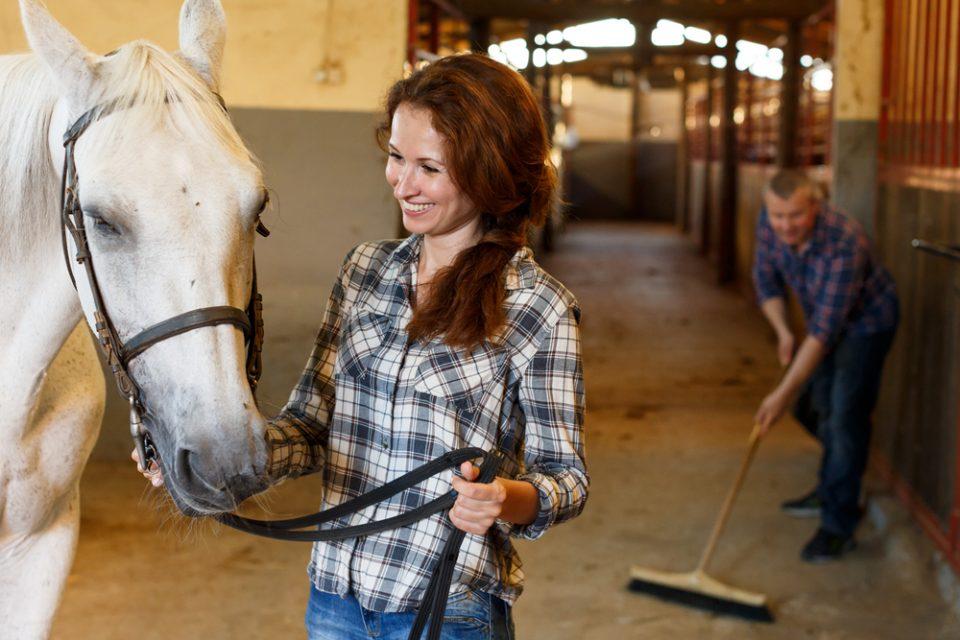 Mulher com cavalo enquanto homem limpa estábulo ao fundo com vassoura e desinfetante